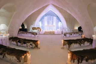 wedding-ceremony-in-ice-castle-snowy-aisle-ice-pews-faux-fur-candlelight-lighting