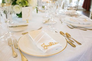 wedding-reception-round-white-table-gold-charger-and-flatware-name-on-top-of-napkin-gold-decoration
