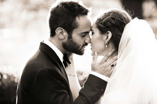 newlywed-couple-in-an-embrace-about-to-kiss-one-another-bride-with-long-veil