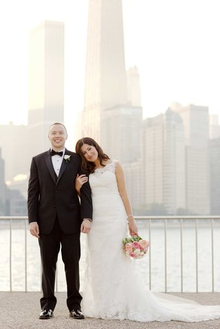 groom-in-tuxedo-with-bow-tie-and-bride-in-wedding-dress-pink-bouquet-in-front-of-chicago-skyline