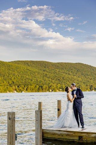 bride-in-custom-hayley-paige-wedding-dress-groom-in-navy-tuxedo-newlyweds-kiss-on-lake-dock