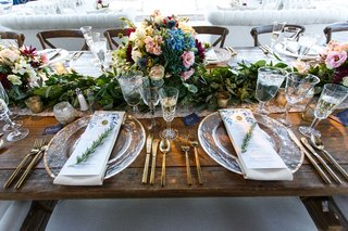 wood-table-with-gold-flatware-charger-plate-sprig-of-rosemary-menu-card-low-centerpiece-vineyard