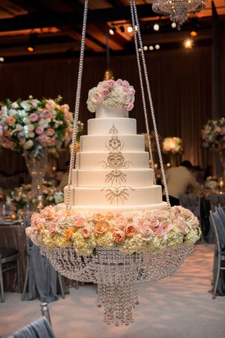 wedding-cake-on-chandelier-swing-with-crystal-rope-details-and-fresh-flowers-sparkling-details