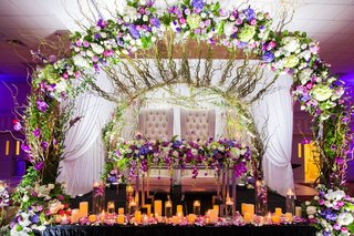 wedding-reception-sweetheart-table-tufted-chairs-arch-of-flowers-candles-reception-ideas-purple