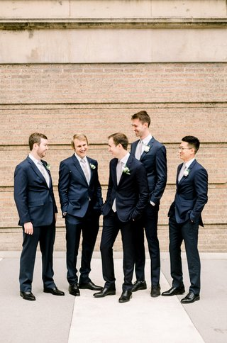 groom-and-groomsmen-in-navy-suits-and-black-dress-shoes-casually-hanging-out
