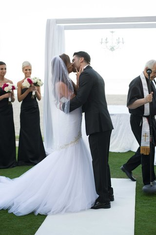 wedding-ceremony-acqualina-resort-and-spa-grass-lawn-white-aisle-runner-mermaid-dress-kiss-husband