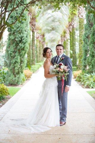 bride-in-strapless-wedding-dress-sheer-side-cutouts-groom-in-grey-suit-florida-wedding