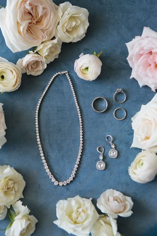 bride-jewelry-and-accessories-wedding-rings-necklace-and-earrings-surrounded-by-garden-rose-flower