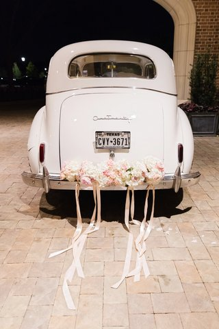vintage-white-getaway-car-with-blush-flowers-and-ribbons-tied-to-the-back