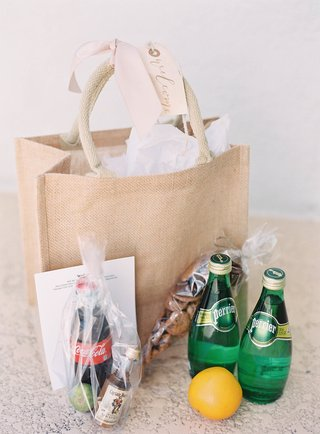 burlap-welcome-bag-with-tag-and-ribbon-coca-cola-captain-morgan-perrier-bottles-snacks-lemon