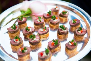 bread-crostini-with-mini-steak-and-garnish-on-platter