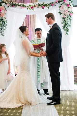 bride-and-tall-groom-standing-in-front-of-catholic-priest