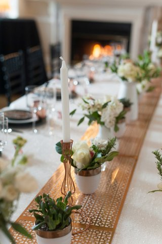 a-copper-table-runner-with-intricate-pattern-under-small-white-and-green-floral-arrangements