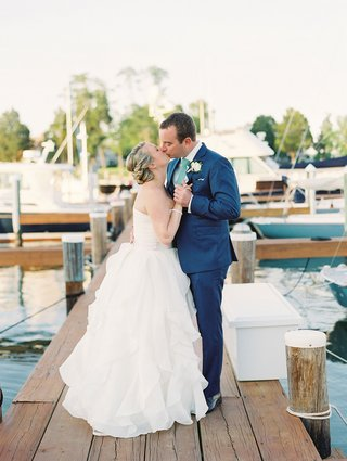bride-in-strapless-ball-gown-kisses-groom-in-navy-blue-suit-and-green-tie-on-wood-dock-wedding-venue