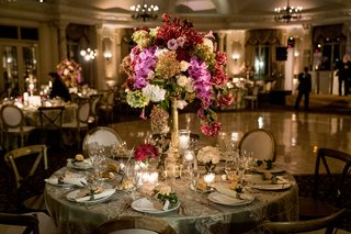ballroom-reception-with-gold-linen-tall-centerpiece-purple-and-burgundy-flowers-gold-chairs-roses