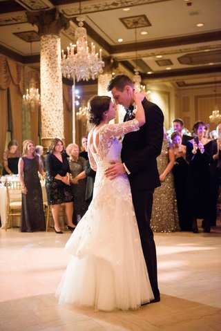 first-dance-bride-in-monique-lhuillier-wedding-dress-bustle-updo-chandeliers-guests-watching
