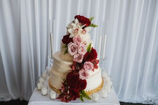wedding-cake-adorned-with-dark-burgundy-flowers-pink-roses-red-and-white-orchids