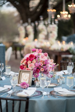 wedding-reception-table-with-dusty-blue-linens-and-small-floral-arrangement-in-shades-of-pink