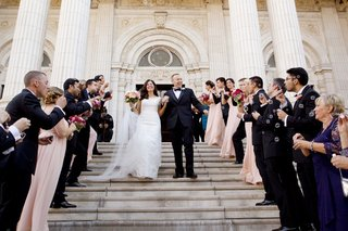 after-ceremony-bride-and-groom-walk-down-steps-with-bubbles-blowing-from-guests
