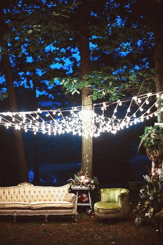 outdoor-wedding-reception-lounge-area-with-vintage-seating-under-a-canopy-of-light-bulbs