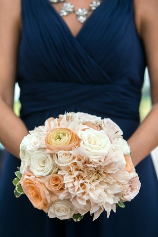 bridesmaid-in-a-sleeveless-navy-dress-holds-bouquet-of-white-roses-peach-ranunculuses-roses-pink