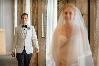 groom-in-white-tuxedo-jacket-bow-tie-glasses-walking-toward-bride-in-veil-and-strapless-gown-wedding