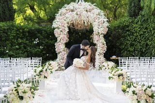 wedding-ceremony-decor-beverly-hills-hotel-pink-and-white-flowers-groom-dips-bride-kiss