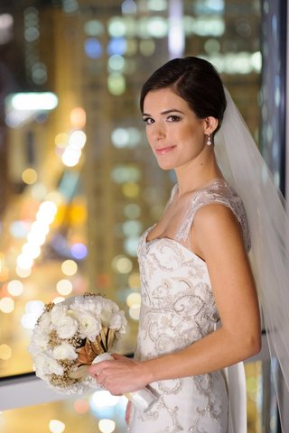 bride-in-monique-lhuillier-wedding-dress-with-white-peony-ranunculus-bouquet-gold-leaves-baby-breath