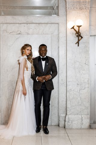 side-cutout-illusion-dress-with-godet-skirt-bow-at-shoulder-groom-in-patterned-suit-jacket-bow-tie