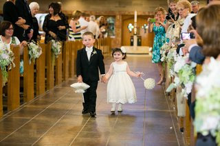 flower-girl-and-ring-bearer-hold-hands-down-church-aisle