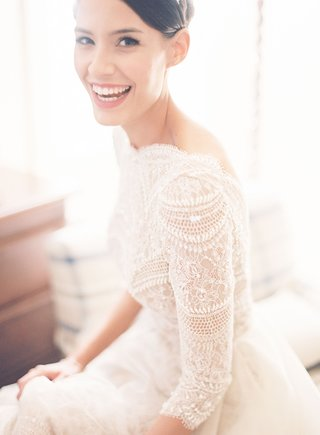bride-in-high-bun-smiling-model-in-lace-wedding-dress-three-quarter-sleeves-and-full-skirt-elegant