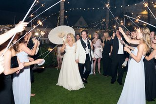 bride-holding-white-parasol-with-groom-for-night-sparkler-exit-twinkle-lights-in-sky