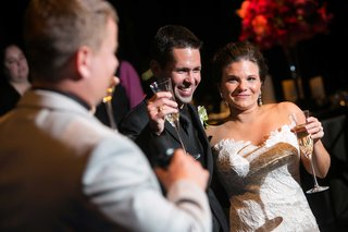 a-bride-and-groom-raise-their-champagne-glasses-in-toast-during-the-reception