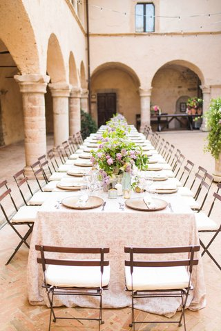 wedding-reception-historic-abbey-arch-pillar-courtyard-long-table-patio-chairs-greenery-lilac-flower