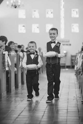 black-and-white-photo-of-two-rings-bearers-walking-down-aisle-pillows-church-maine-wedding-smiling