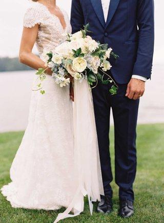 bride-in-carolina-herrera-wedding-dress-groom-navy-blue-tuxedo-bouquet-with-garden-rose-ribbon