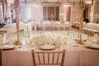 reception-ballroom-with-rectangular-table-with-linens-ivory-flowers-gold-candelabra-wedding-ideas
