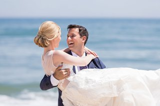 wedding-portrait-bride-with-blonde-hair-pretty-updo-groom-holding-her-on-beach-in-montauk