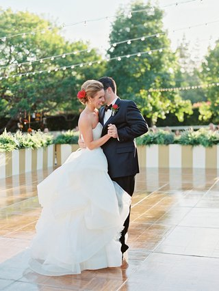 bride-in-vera-wang-wedding-dress-with-red-flower-in-hair-dances-with-groom-on-large-dance-floor