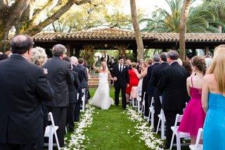 newlyweds-walking-up-petal-lined-grass-aisle