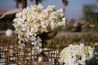 gold-ceremony-chairs-with-gold-urns-on-riser-with-white-hydrangea-rose-tulip-and-orchid-flowers