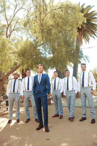 tim-lopez-in-navy-blue-groom-suit-with-groomsmen-in-light-grey-pants-suspenders-ties-brown-shoes