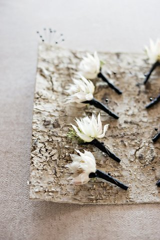 white-single-flower-boutonnieres-greenery-black-fabric-wrapped-around-pins