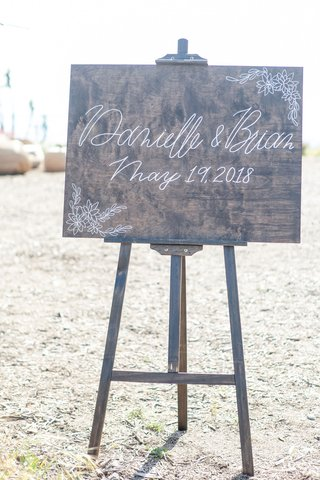 wedding-ceremony-outdoor-wood-sign-with-modern-calligraphy-in-white-names-and-wedding-date-easel