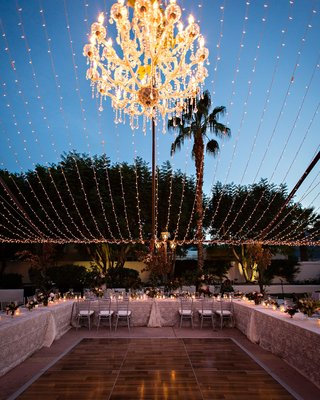 reception-tables-around-dance-floor-string-lights-silver-chairs-u-shape-low-centerpieces