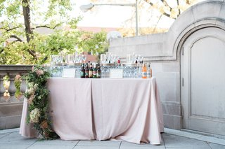 wedding-reception-cocktail-hour-pink-linen-tablecloth-bar-area-with-beer-and-flower-runner