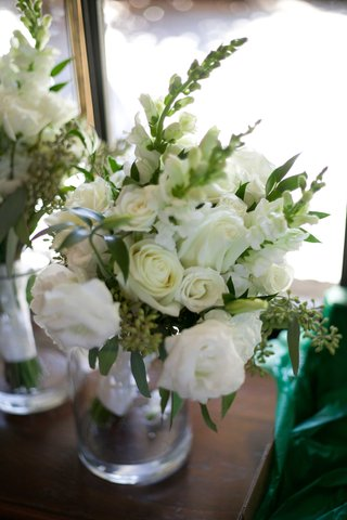 bridesmaid-bouquet-with-white-flowers-roses-and-green-leaves-foliage-in-glass-vase