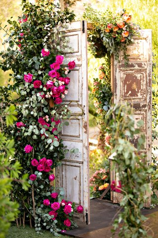 wedding-reception-ceremony-decor-wood-doors-with-pink-roses-greenery-flowers-decor-outdoor