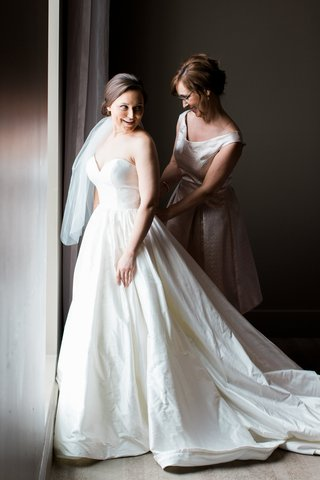 bride-in-justin-alexander-plain-ball-gown-mother-of-the-bride-fastens-dress
