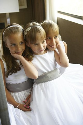 three-flower-girls-with-bangs-and-grey-sashes-on-white-dresses